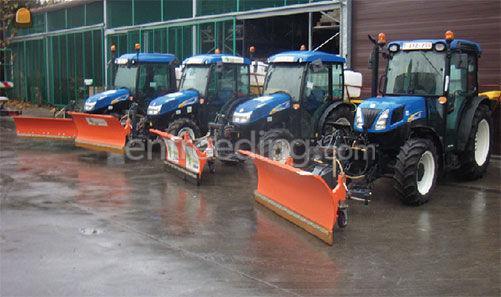 tractor met sneeuwschuif en zoutstrooier