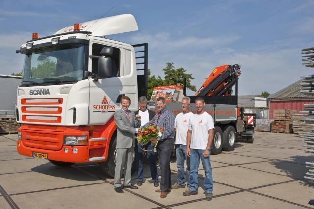 Blije gezichten bij de overdracht van de nieuwe Scania R400 XPi aan de Scholtens Groep. De heer Guido Scholtens, algemeen directeur van de Scholtens Groep neemt de sleutels en de bloemen in ontvangst uit handen van Jurgen Jacobsen (M) van Scania Zwaagdijk