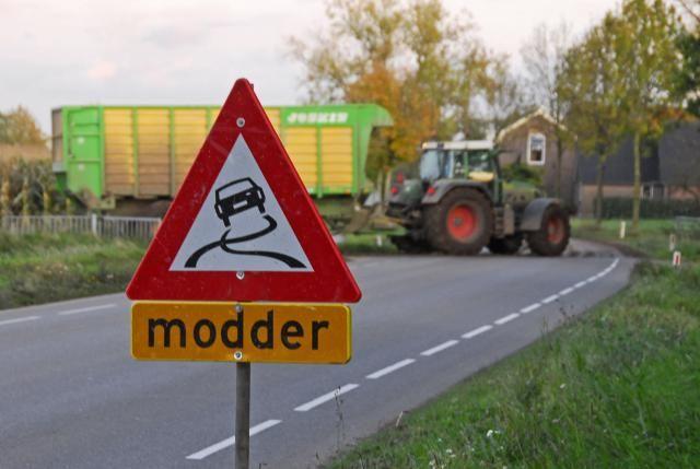 Bord modder op de weg en tractor met silagewagen