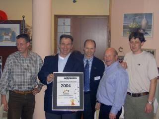 Op de foto: Ruud Hoogerhuis, William van der Kleij, Oene Rozendal en Mark Beekmans van Kuiken Cramat nemen het certificaat voor beste Sennebogen dealer van het jaar 2004 in ontvangst van de heer E. Sennebogen Jr (midden).
